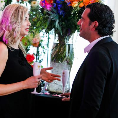 Twee personen die spreken in een feestzaal tijdens een bedrijfsfeest.